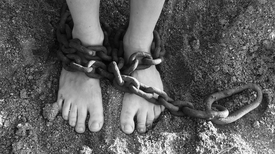 Esclavo con una cadena en los pies encima de tierra