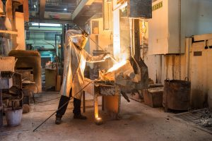 Empresa de fundición afiliada a Mutua Navarra donde e ve a uno de sus empleados realizando las tareas de volcado del metal fundido.