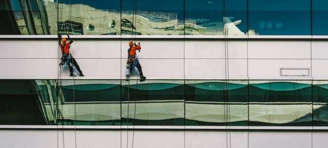 Personas limpiando un edificio colgados por una cuerda