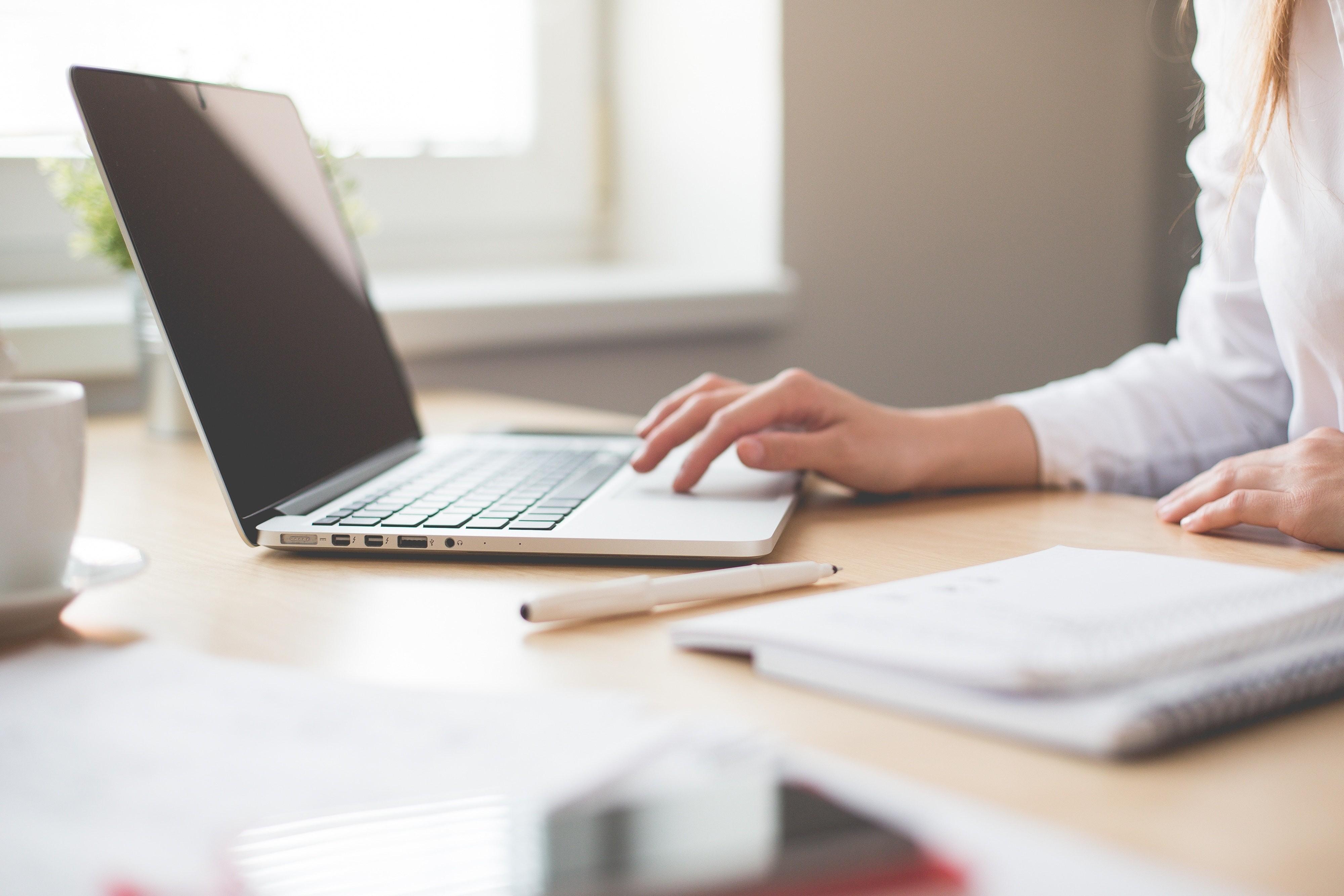 Chica en una oficina, mesa de despacho con cuaderno y ordenador