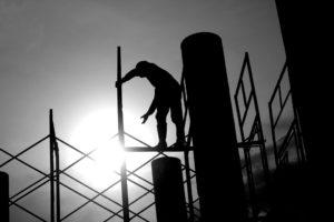 Operario de la construcción subido a un andamio con riesgo de caerse.