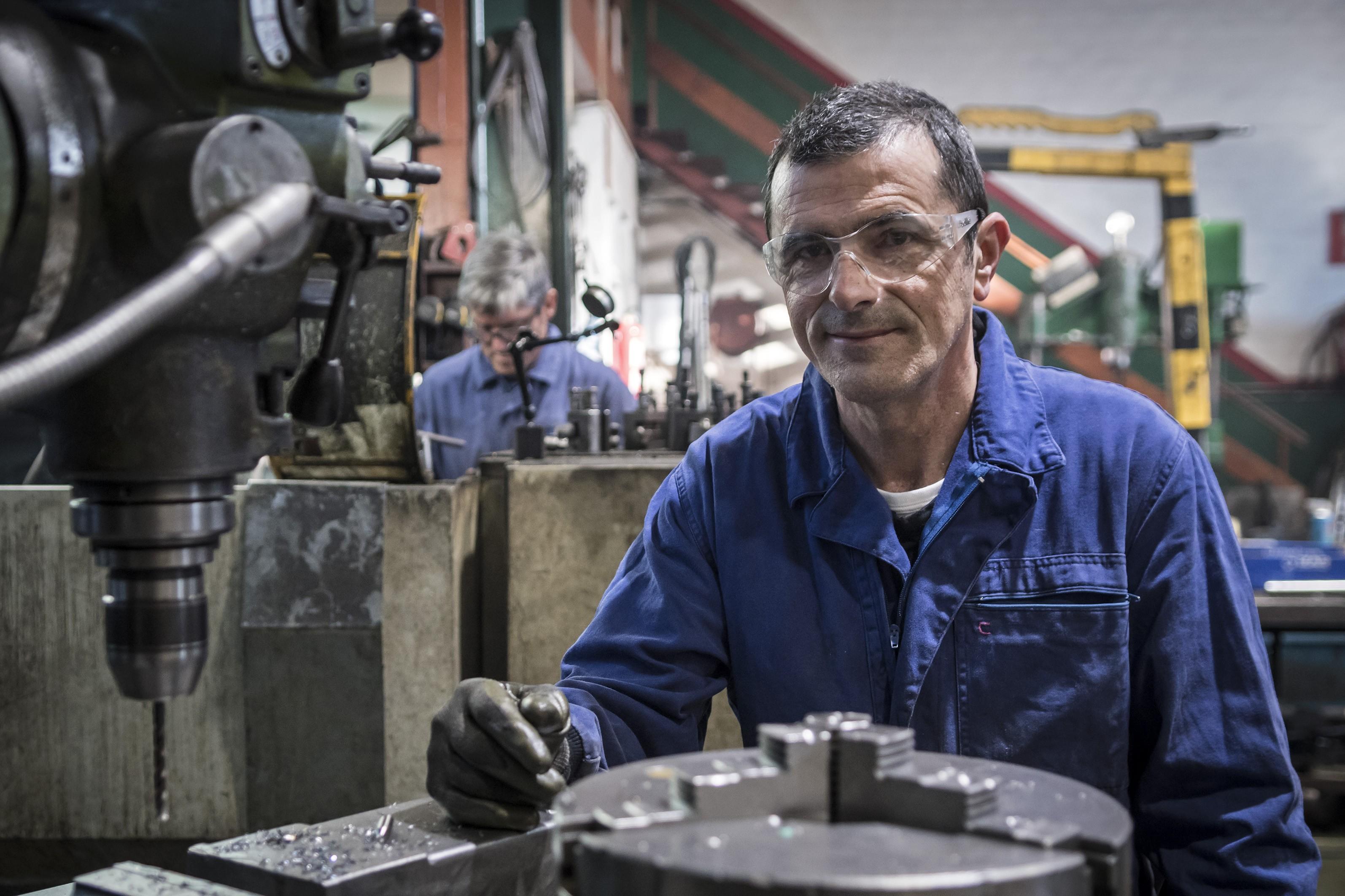Carlos Remiro López, tornero fresador en el taller con su compañero de fondo
