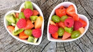 Cuencos en forma de corazon con fruta saludable dentro