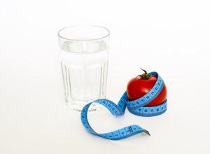 Imagen de un vaso de agua, una manzana y un metro