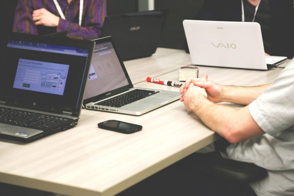 Foto de ordenadores portátiles y personas en una reunión