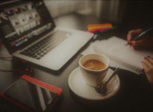 Foto de una persona trabajando con un ordenador portátil, una libreta, y un café