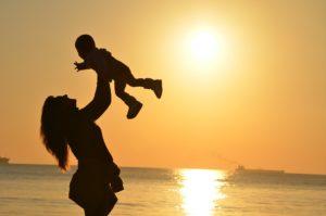 Foto de una mujer levantando a un niño con el sol de fondo